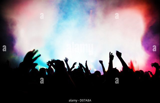 People with hands up having fun on a music concert / disco party. - Stock Image