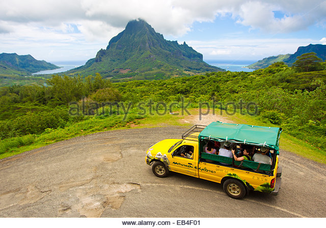 Tourists on a guided tour at Le Belvedere Lookout, overlooking Opunohu Bay and Cook Bay. - Stock Image