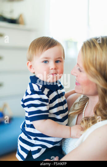 Sweden, Portrait of boy (18-23 months) with mother - Stock Image