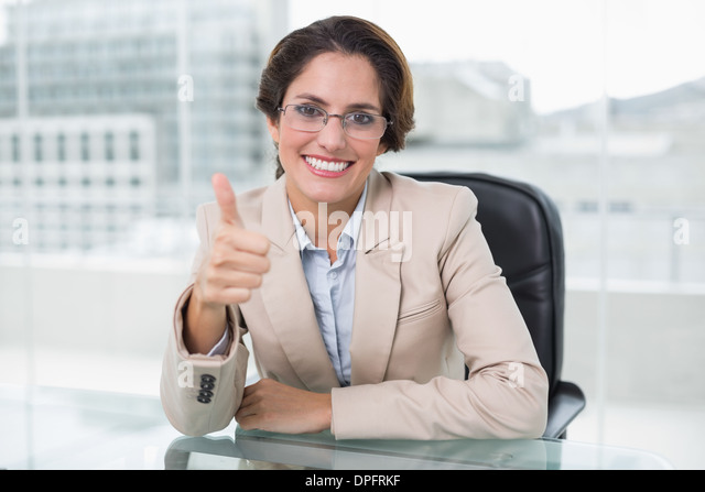 Smiling businesswoman showing thumb up at her desk - Stock Image
