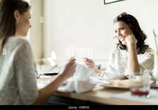 Two gorgeaus ladies eating in a restaurant while having a conversation - Stock Image
