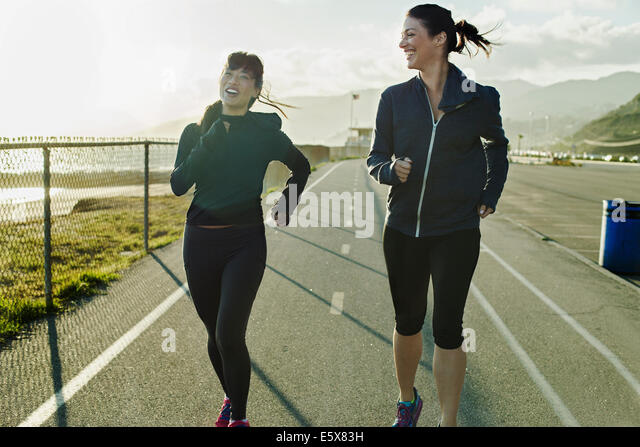 Joggers running on road - Stock Image