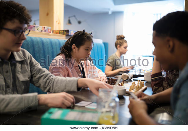 Focused Asian tween girl playing chess with friend at cafe table - Stock Image