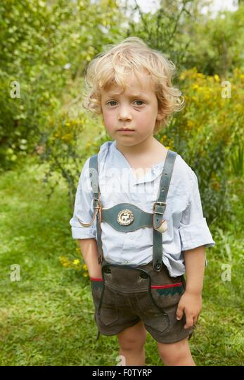 Portrait of sad boy with scratched face wearing lederhosen - Stock Image
