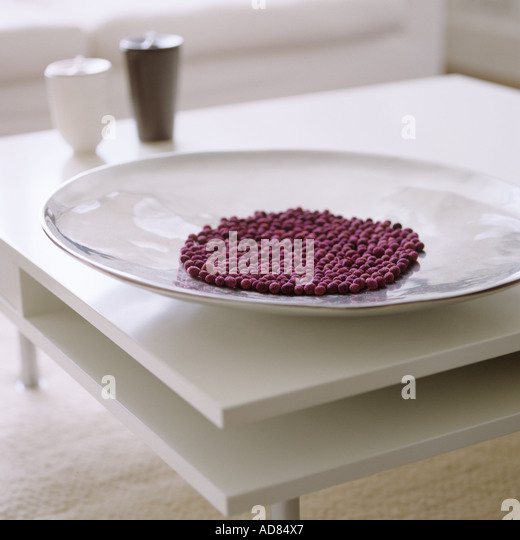 dried purple beans in a white dish on a white coffee table - Stock Image