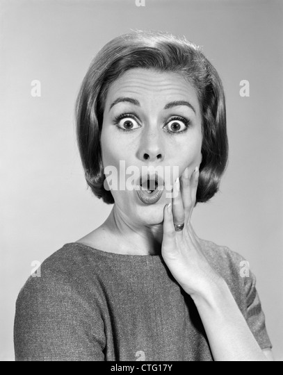 1960s PORTRAIT WOMAN WITH HAND ON CHEEK LOOKING AT CAMERA WITH SHOCKED EXPRESSION - Stock Image