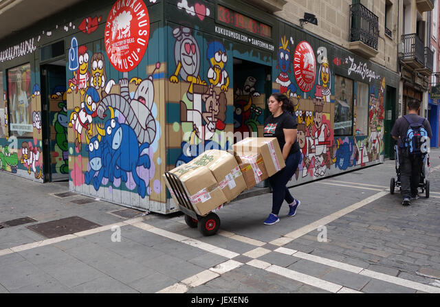 Woman delivering stock to shop in Pamplona in Northern Spain - Stock Image