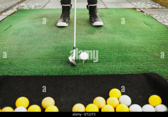 Low section of woman aiming golf ball at driving range - Stock-Bilder
