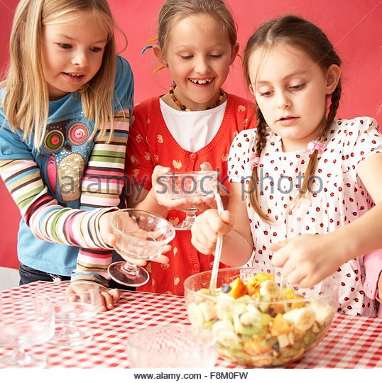 Three girls eating fruit salad - Stock Image
