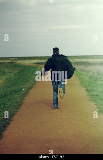 Middle aged man running in rural coastal area - Stock-Bilder
