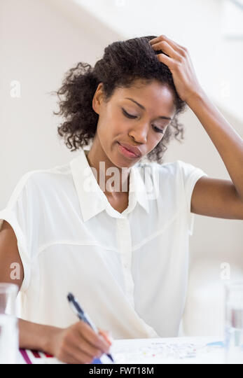 Tense businesswoman writing a report - Stock Image