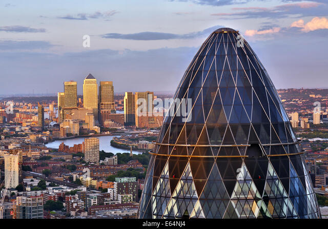 General view of buildings of the city skyline, Canary Wharf and the Gherkin, 30 St Mary Axe at dusk in London, England - Stock Image