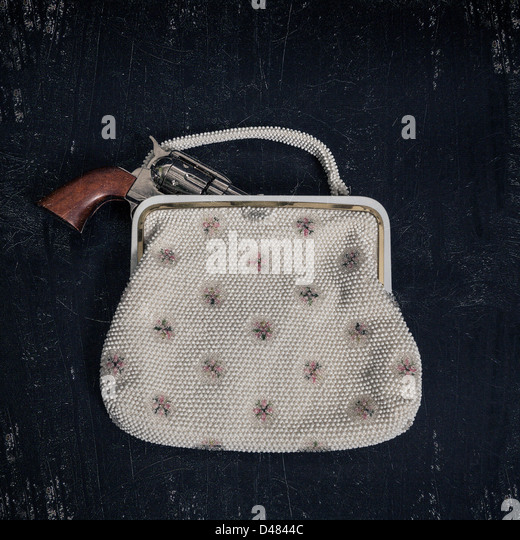a gun in an elegant handbag - Stock Image