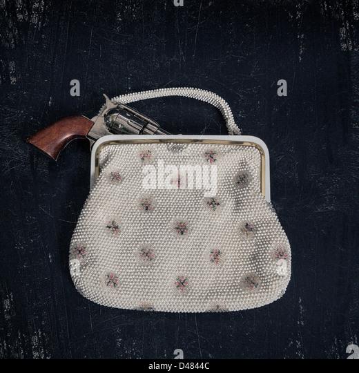 a gun in an elegant handbag - Stock Image