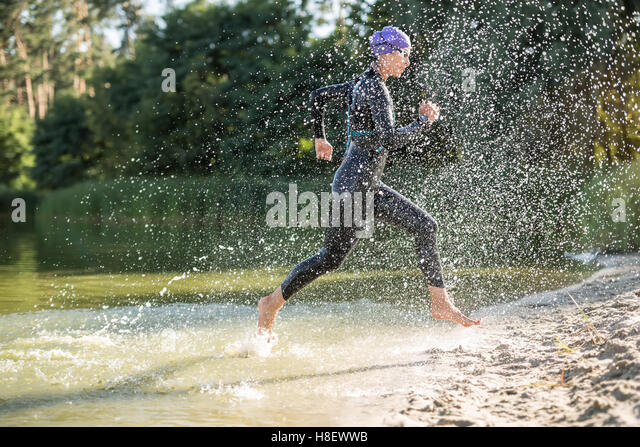 Sportive girl runs on the waterfront - Stock-Bilder