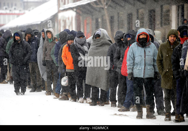 Belgrade, Serbia. 11th Jan, 2017. Refugees and migrants stand in line for food distribution outside an improvised - Stock Image