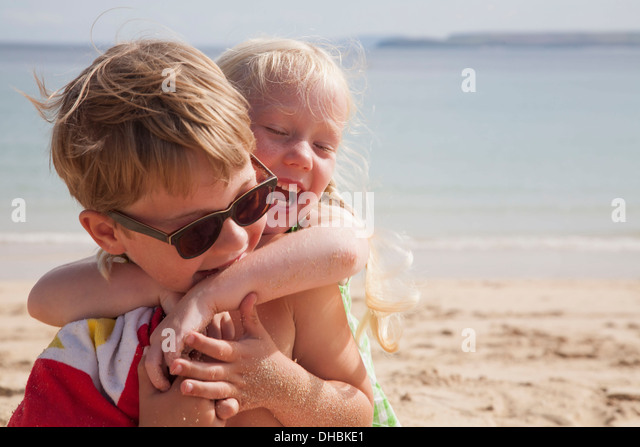 A brother and sister play fighting on the beach. A boy in sunglasses and a younger girl with her arms around his - Stock Image