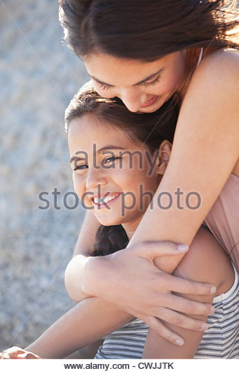 Mother hugging smiling daughter - Stock Image