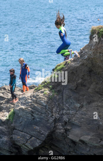A young teenager tombstoning off cliffs in Newquay, Cornwall. - Stock Image