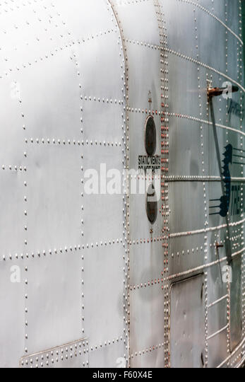 Airplane, side of silver coloured metal  fuselage showing panelling and bolts - Stock Image