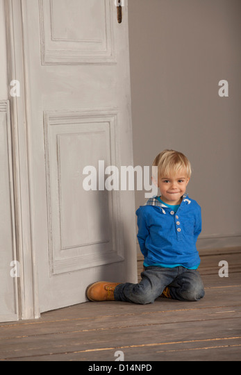 Boy sitting on wooden floor - Stock Image