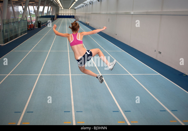 female athlete doing crazy star jump - Stock Image