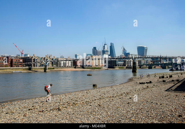 River Thames foreshore at low tide with view towards the City of London. - Stock Image
