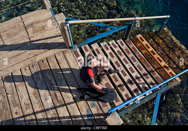Snorkeler sitting on steps to water - Stock-Bilder