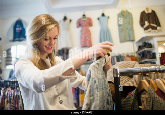 Woman looking at top garment - Stock-Bilder