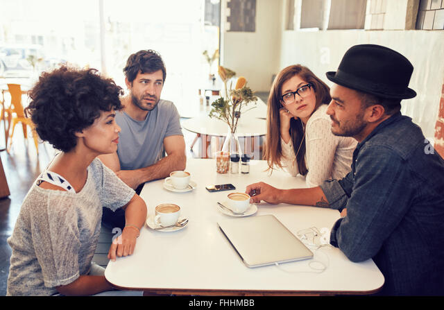 Portrait of young men and women sitting at a cafe table and talking. Group of young friends meeting at a coffee - Stock-Bilder
