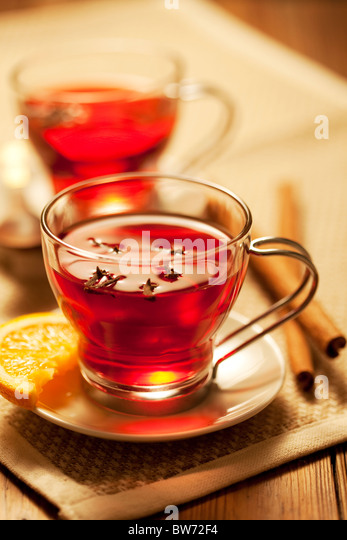 inviting warm spicy drink with ingredients - Stock Image