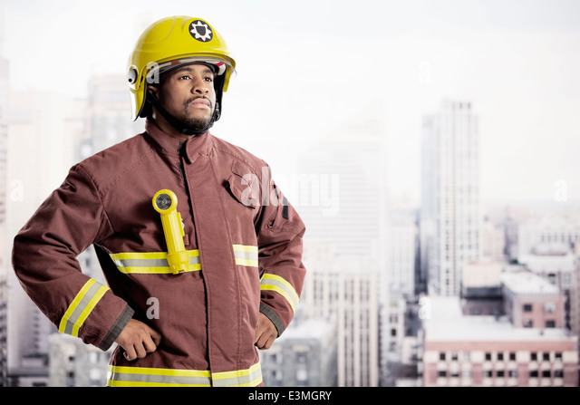 Portrait of confident fireman in urban window - Stock Image