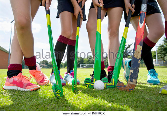 Legs of middle schoolgirls playing field hockey in physical education class - Stock-Bilder