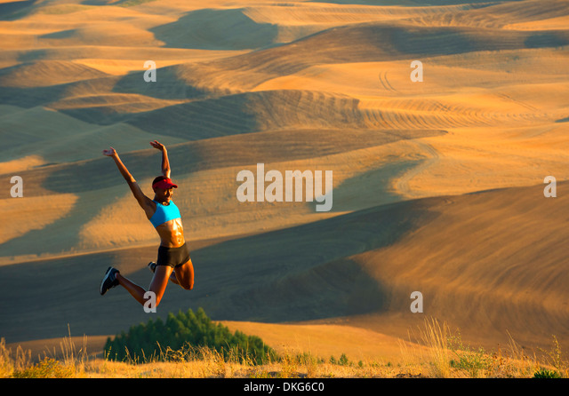 Young female runner jumping for joy in fields, Bainbridge Island, Washington State, USA - Stock Image