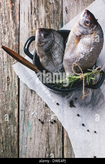 Top view on tow raw dorado fish with rosemary and sea salt server in black pan over old wooden table. See series - Stock Image