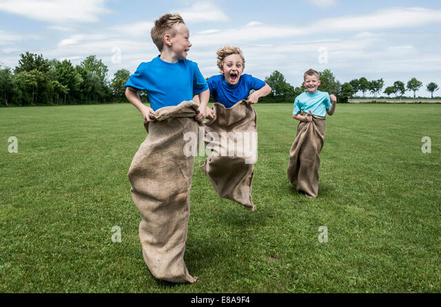 Three young boys running in sackrace jumping - Stock-Bilder
