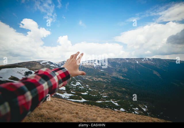 Scenic landscape with human hand in foreground - Stock Image