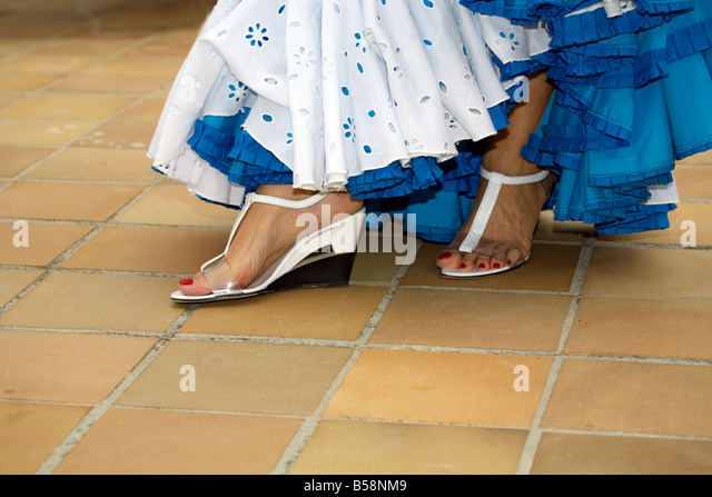 Feet of beautiful middle aged Spanish woman in traditional costume at the Fuengirola Feria, Costa del Sol, Spain, - Stock Image