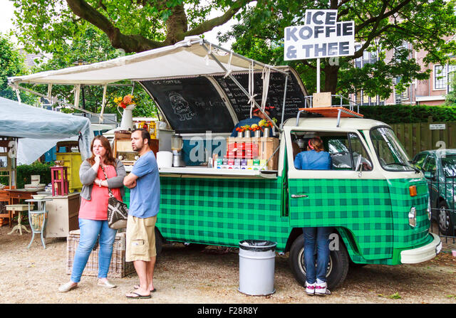Serving drinks out of an old timer bus decorated with retro artifacts, a couple waits while the drink is prepared. - Stock Image
