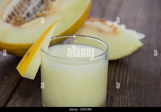 Fresh made Honeydew Juice with fruit pieces on wooden background - Stock Image