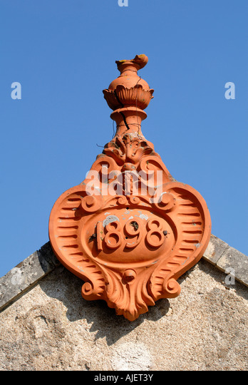 Terracotta roof detail dated 1898, Vienne, France. - Stock Image