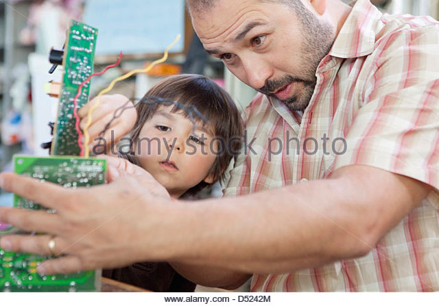 Father and son playing with microchips - Stock Image