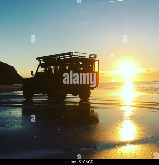 Land Rover on beach in sunset - Stock-Bilder