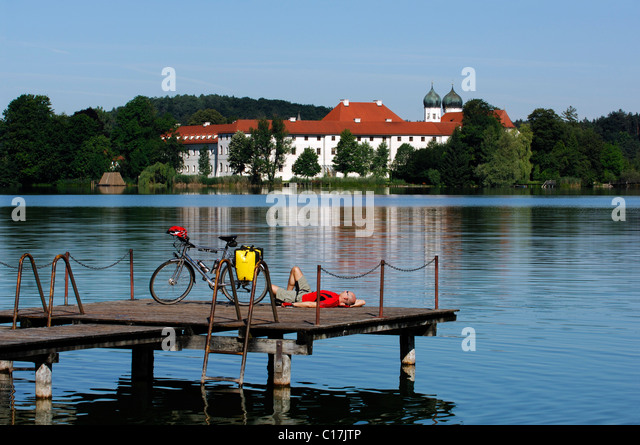 Bicyclists on jetty in front of Seeon Abbey, Chiemgau, Bavaria, Germany, Europe - Stock Image