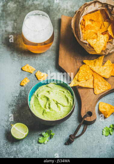 Mexican corn chips, fresh guacamole sauce and glass of beer on wooden serving board over grey concrete table background, - Stock Image