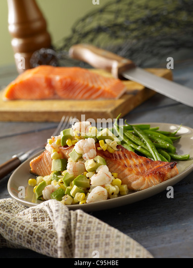 Grilled salmon topped with shrimp and avocado and served with green beans - Stock Image