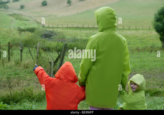Green meadow with plastic waterproof coat colorful family in front - Stock-Bilder
