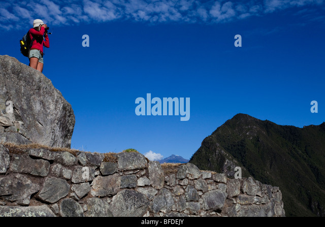 A young girl wearing red takes a picture while standing on an ancient ruin. - Stock Image