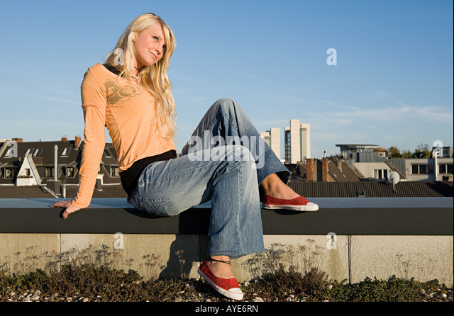 Young woman sitting on a ledge - Stock Image