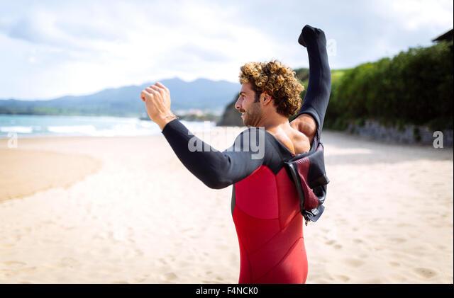 Spain, Asturias, Colunga, surfer preparing on the beach - Stock Image